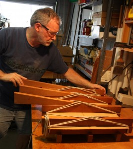 Inserting Mahogany wedges under the ropes to tighten.