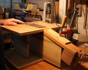 The guitar neck clamped in the headstock routing jig.