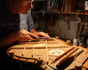 Carefully maneuvering the chisel to shape the brace and to avoid cutting into the top or a finger.