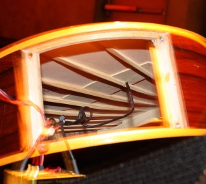 A peak inside her harp guitar while changing the battery - fan bracing for a nylon string instrument.