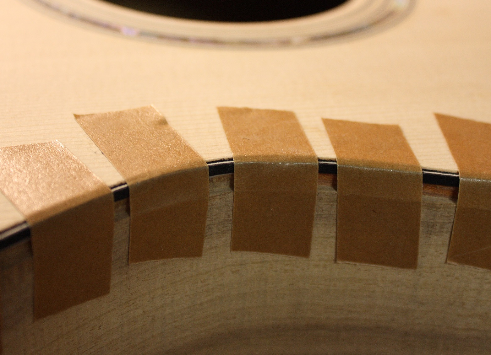 Binding tape is used to hold the purfling in the channel until it dries.